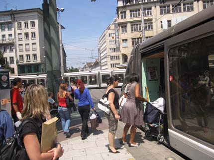 PHOTO: A woman with a stroller boards a tram.