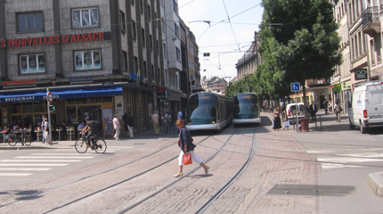 PHOTO: A woman walks in front of two trams.