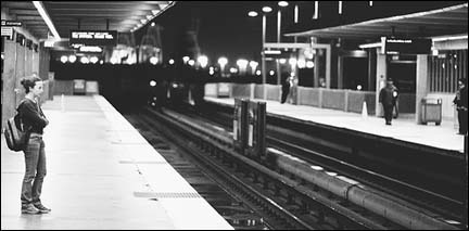 A lone woman waits for a train.