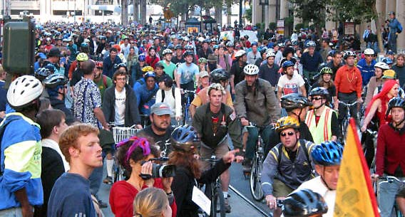 Image of hundreds of bike riders on an urban city street with people watching them ride by.