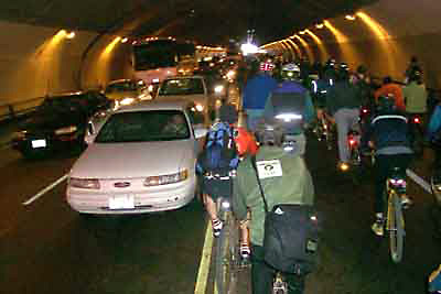 Image of many bike riders in a tunnel with cars.
