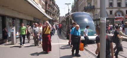 Photo: Lots of pedestrians and a tram sharing space.